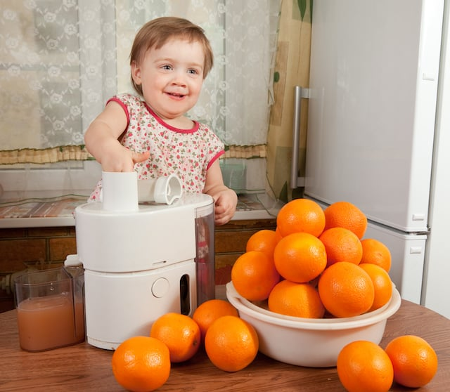 basic life skills for kids- girl making orange juice
