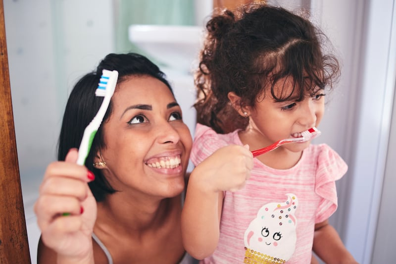 Child brushing teeth with mom- how to teach your child to be independent