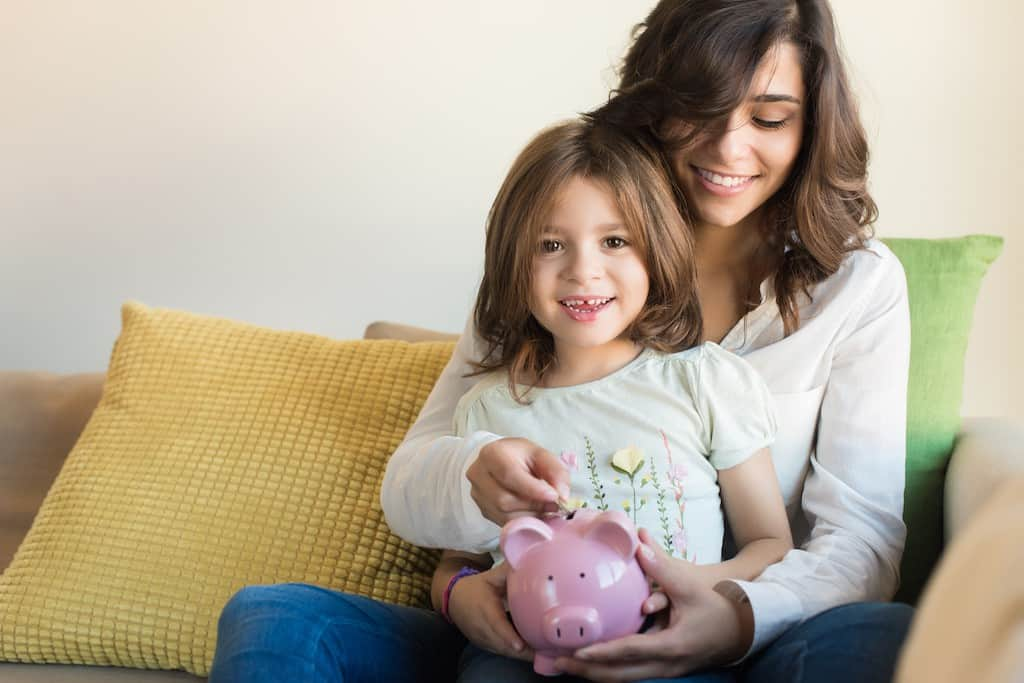 How to raise grateful kids - mom and daughter putting money in piggy bank