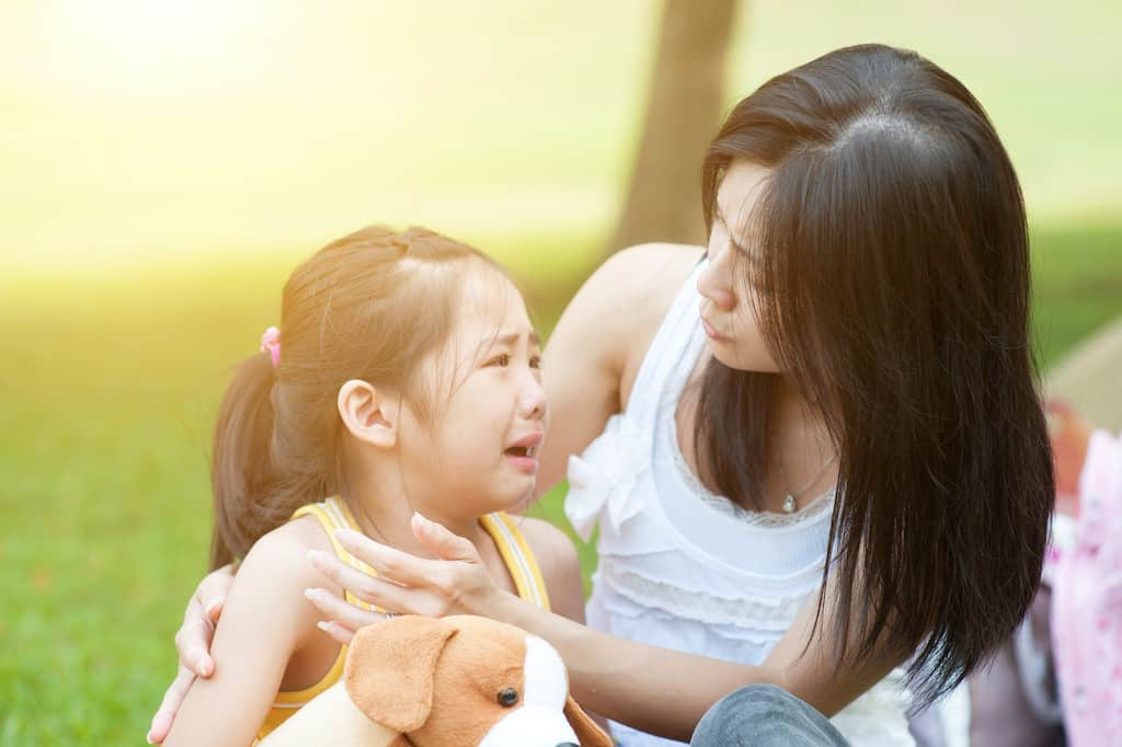 Mom comforting crying girl- How to stop sibling rivalry