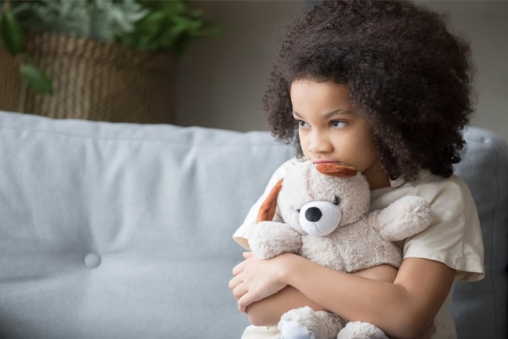 a lonely child hugging her teddy bear