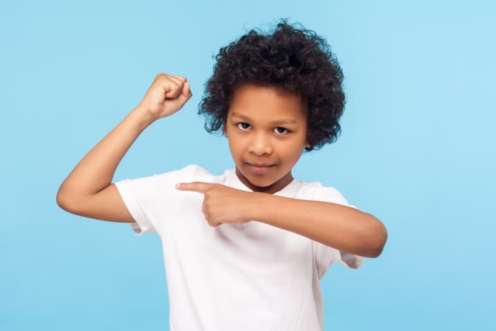 boy showing his muscle-hugging improves immunity
