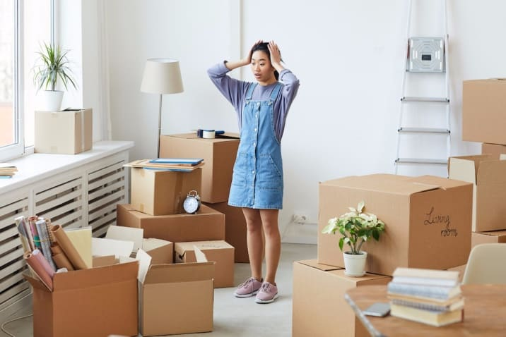 A woman feeling overwhelmed and distracted by clutter - decluttering mistakes to avoid