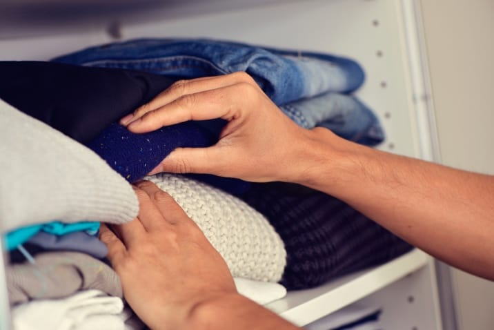 A man going through his clothes - decluttering mistakes to avoid