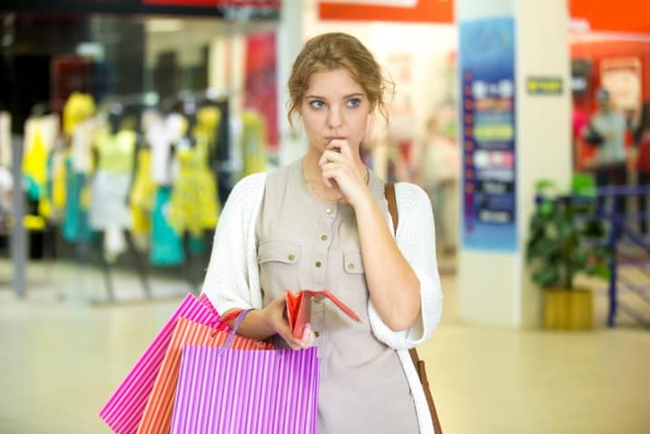 a woman thinking about a purchase - how to stop accumulating clutter
