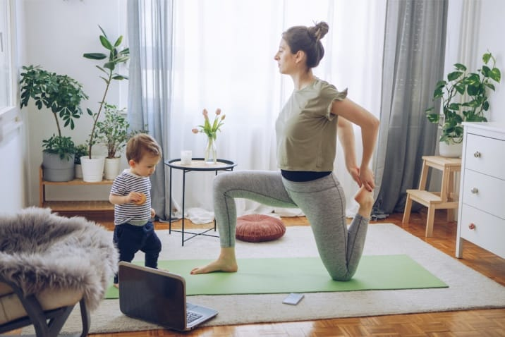 a mom doing yoga while kid is running around